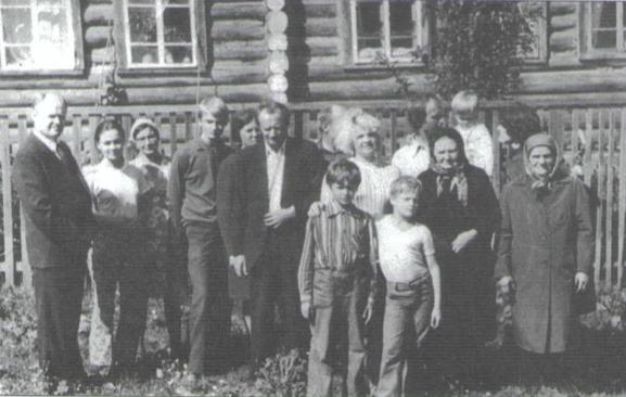 Семья Галановых (часть семейства) на фоне родового гнезда – дома в котором родились семь сыновей